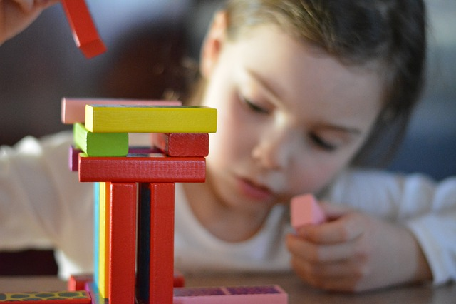 young child playing with building blocks