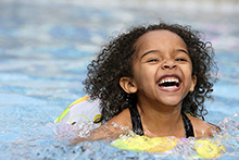 image of a young African-American girl happily swimming in a pool